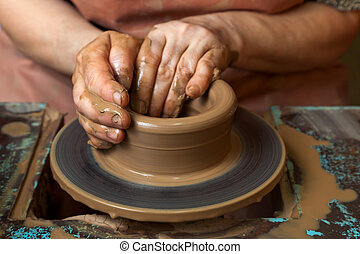 The hands of a potter, creating an earthen jar on the circle, close-ups