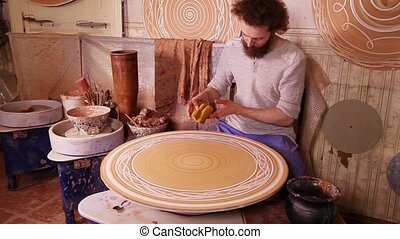 Potter creating a decorative panel