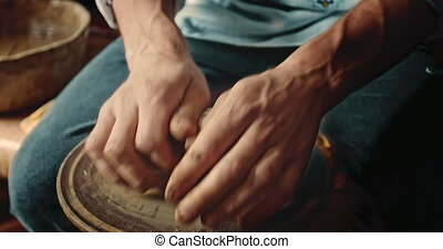 Potter Crushing Clay - Close up of potter's hands crushed...