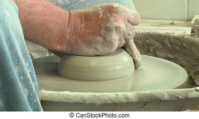 Potter flattens clay on wheel