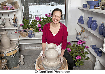 Potter in workshop - Potter with finished vase on pottery...