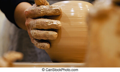 Potter is making clay pot on the potter's wheel