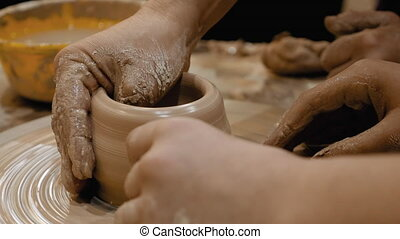 Potter is making clay pot on the potter's wheel - Potter is...