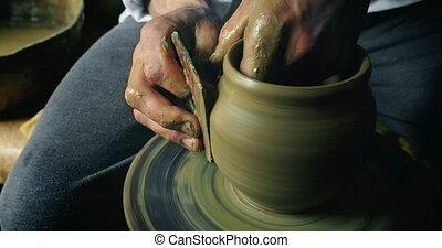 Potter Makes Clay Vase - Potter makes vase shape using wheel...