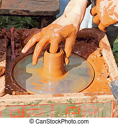 Potter makes on pottery wheel clay pot.