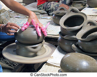 Potter makes on the pottery wheel clay pot. The hands of a potter with the tool, close-up.