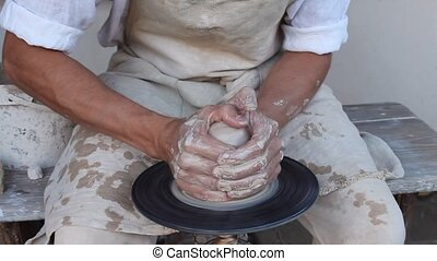 potter making a clay jug