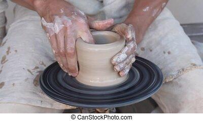 potter making clay jug