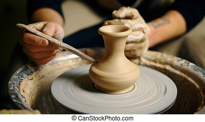 Potter modeling ceramic pot from clay on a potter's wheel....