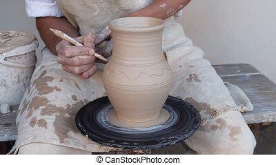 Potter painting a clay jug