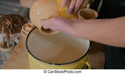 Potter preparing ceramic wares for burning - Professional...