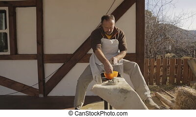 Potter sculpt at wheel machine in gray clay. Man in white apron work outside at porch