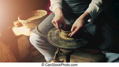 Potter Shapes Clay Jug - Potter's hands makes clay jug on a...