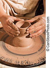 Potter Shaping Clay - Closeup on hands of potter shaping...