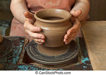 Potter shows just created a pot - The hands of a potter,...