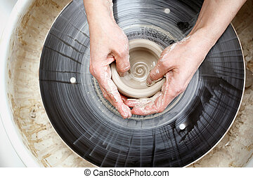 Potter wheel. - Woman leaping clay pots on a potter's wheel.