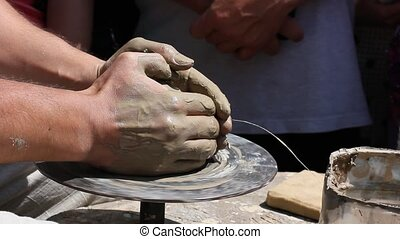 Potter's hands working clay on pott