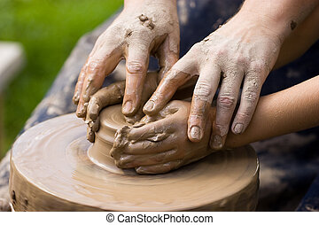 Potters team - A potters hands guiding a child hands to help...