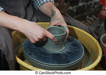 potter's wheel and hands of craftsman
