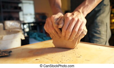 Pottery and ceramic. Sculptor is pugging and kneading clay...
