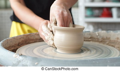 Pottery class workshop. Clay shaping on potter's wheel. Potter teaches his craft to the children.