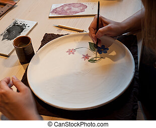 pottery painting - man paints beautiful ornaments on ceramic...