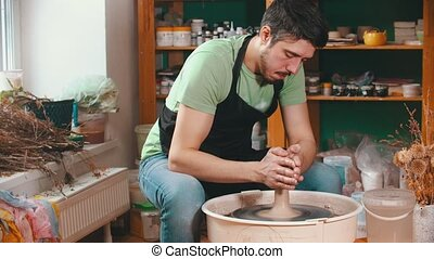 Pottery - the master is wetting the clay for better glide - indoor