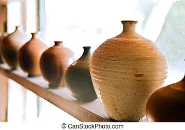 handmade pots/vases on a shelf at workshop