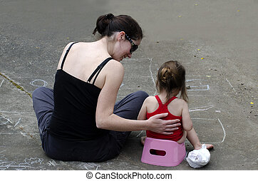 A young mother trains her daughter to use the potty outdoor.
