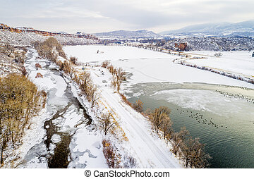 Poudre River, lake with water fowl and Colorado foothills - aerial view of winter scenery