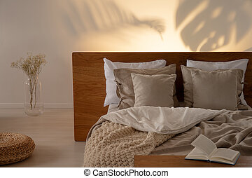 Pouf and flowers next to bed with headboard and pillows in bedroom interior with book. Real photo