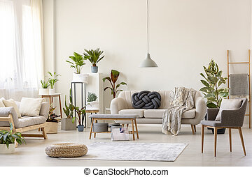 Pouf on rug and plants in spacious living room interior with grey chair near beige couch. Real photo