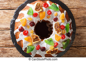 Pound cake with dried berries and fruits and frosting close-up on a board. horizontal top view