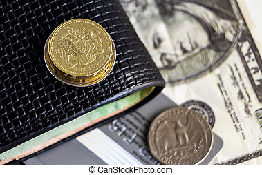 Pound coin, old dollar coin and banknote with wallet on the table. The concept of the main currency exchange can be used worldwide.