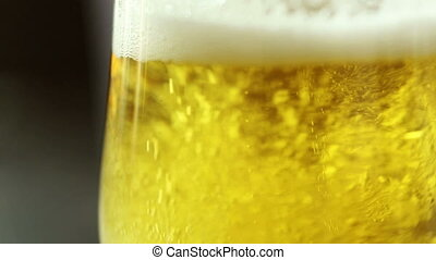 Pour beer into a glass on dark wooden table
