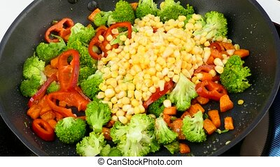 pour corn kernels into a frying pan with fried vegetables -...