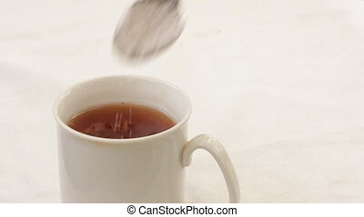 Pour into a cup of tea sugar with a teaspoon