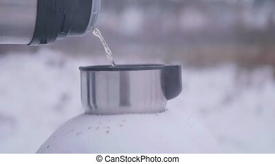 pour the hot tea into the Cup in the winter in the open air