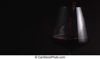 Pour the red wine into a glass in close-up. Expensive drink for a celebration in a restaurant. Isolated, black background, professional lighting 4k