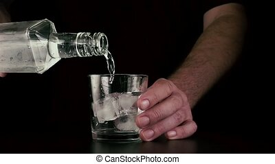 Pour vodka from a bottle into a glass with ice. Slow mo