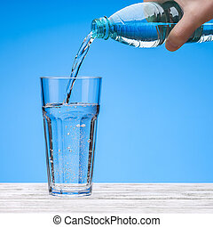 Pour water from plastic bottle into large glass. Bottle in hand of man.