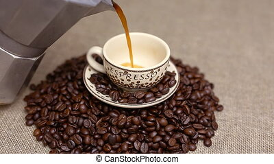 Pouring a cup of coffee with coffee beans