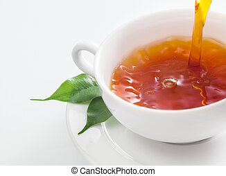 Close up view of someone pouring a cup of refreshing tea into a plain white cup with fresh green tea leaves resting on the saucer on a white background