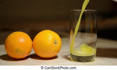 Pouring a glass of freshly squeezed orange juice from...