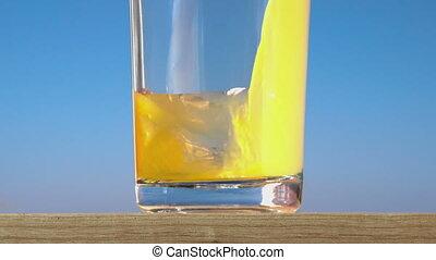 pouring a glass of orange juice creating splash. slow motion
