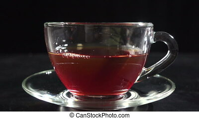 Pouring a milk in transparent cup with hot tea, slow motion