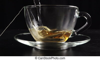 Pouring a tea in transparent cup with hot water and teabag,...