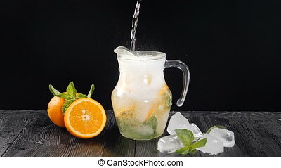 Pouring Aerated cold water in transparet jar with sliced orange and ice cubes. Slow motion. Black background. Bartender making summer fresh cocktail. cocktail party, nightlife and nightclub. Full hd