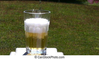 Beer - Pouring An Ice Cold Beer Into A Glass Outside In...