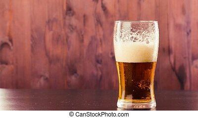 pouring beer in glass with white foam on wood table...